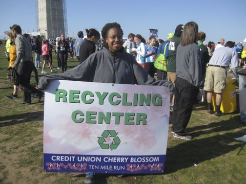 volunteer with recycling sign